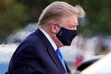 Donald Trump wears a mask and looks down.