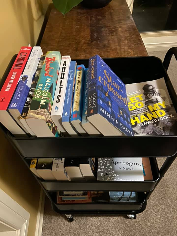 A small three-tier trolley loaded with books on each tier.