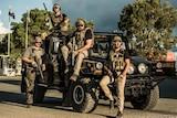 Four men wear army gear.