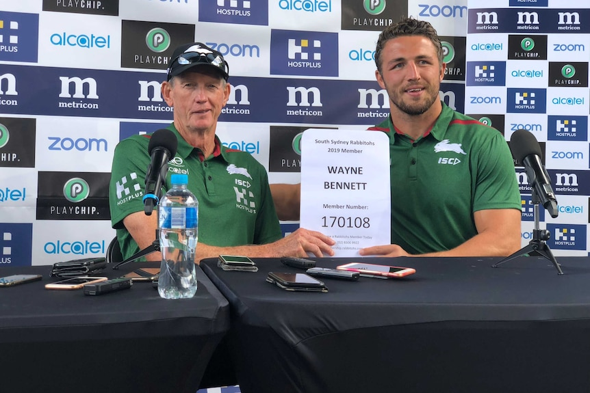 Wayne Bennett and Sam Burgess hold up Bennett's South Sydney membership certificate at a Rabbitohs media conference.