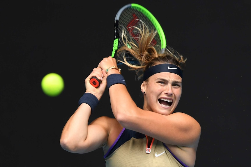 Aryna Sabalenka screams as she hits a shot, holding her yellow tennis racquet above and behind her head