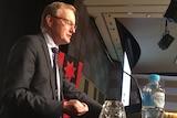 RBA governor Philip Lowe speaks at a podium