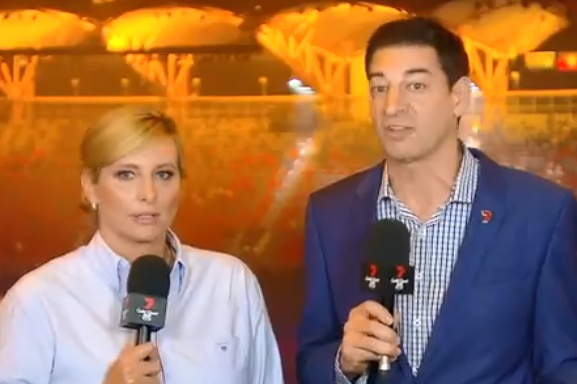 Hosts Johanna Griggs and Basil Zempilas stand together, stadium in the background.