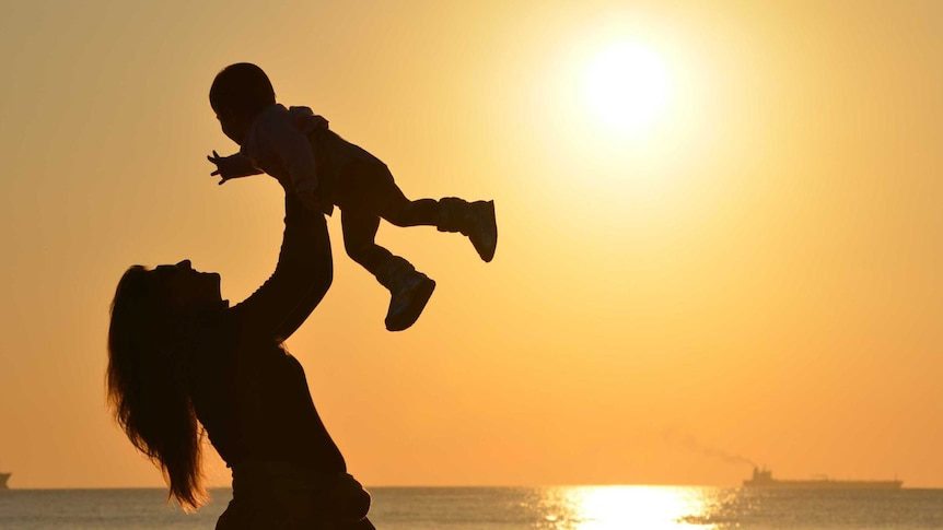 Silhouette of woman holding child in the air for a story about how people dealt with motherhood indecision.