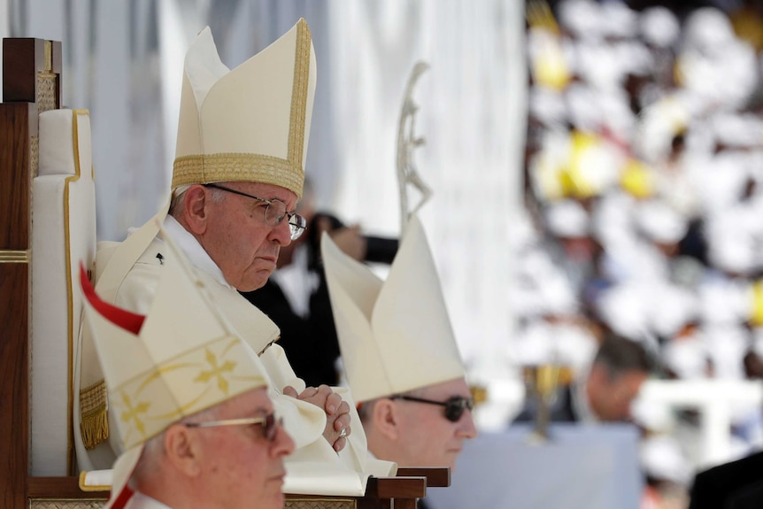 Pope Francis sits in front of the altar as he celebrates a mass at a sports stadium in Abu Dhabi, UAE.