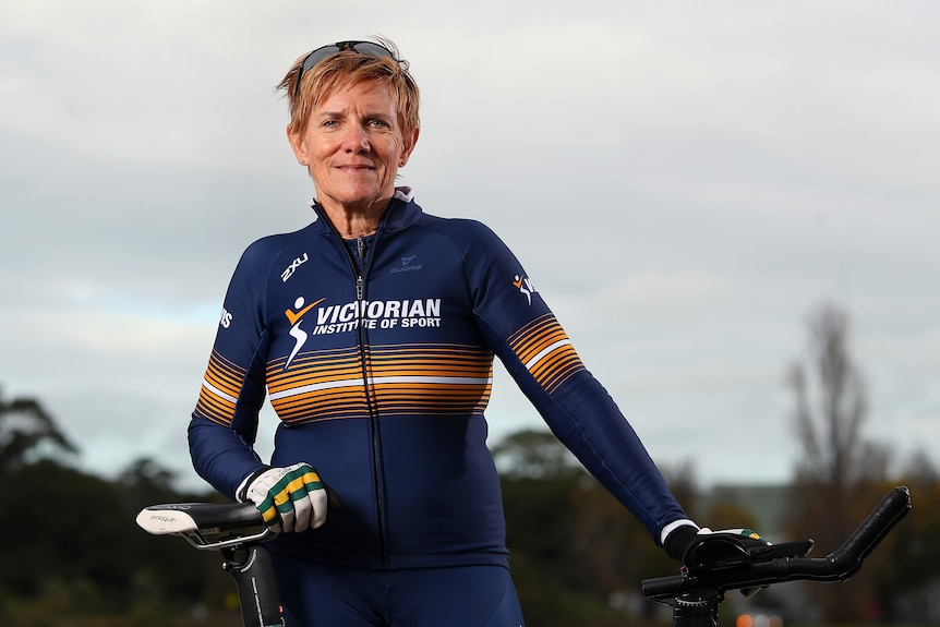 Female cycling standing with her bike
