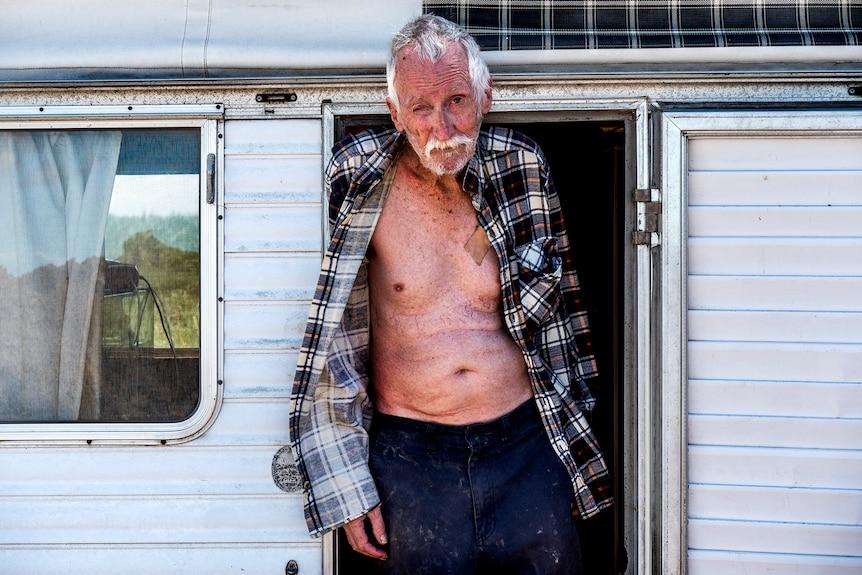 An elderly man stands in a caravan doorway.