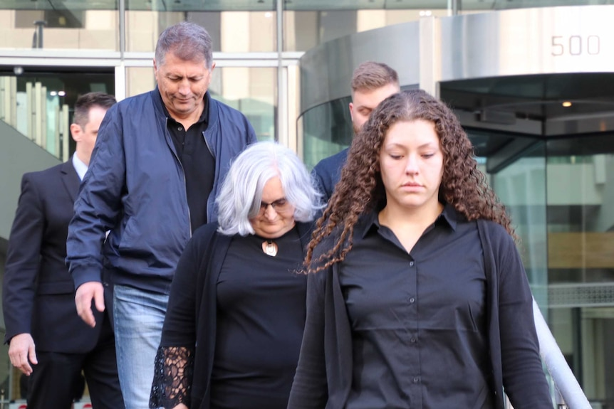 A younger and an older woman walk out of the Perth District Court in Perth with their heads down and with a man behind them.