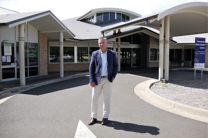 a man stands in front of a modern hospital