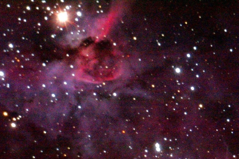 A combination of pink and purple colours with white stars scattered throughout space.