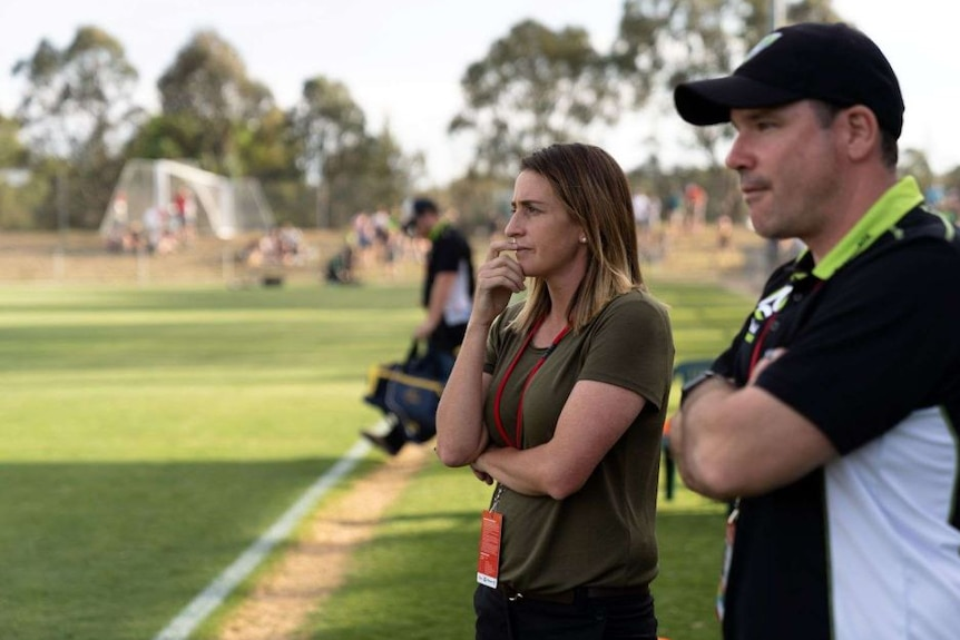A women's soccer coach stands pitch-side with her hand in front of her mouth, watching a match.