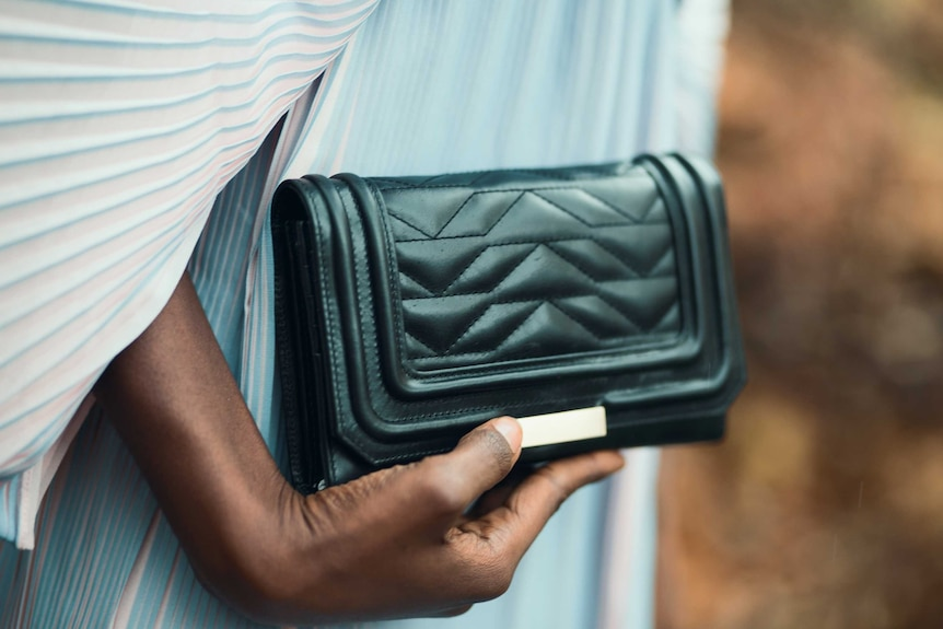 Close up of woman holding a black purse, showing that carrying cash is a good way to save your money.