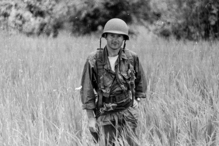 Derek Maitland standing in a field dressed in conflict apparel.
