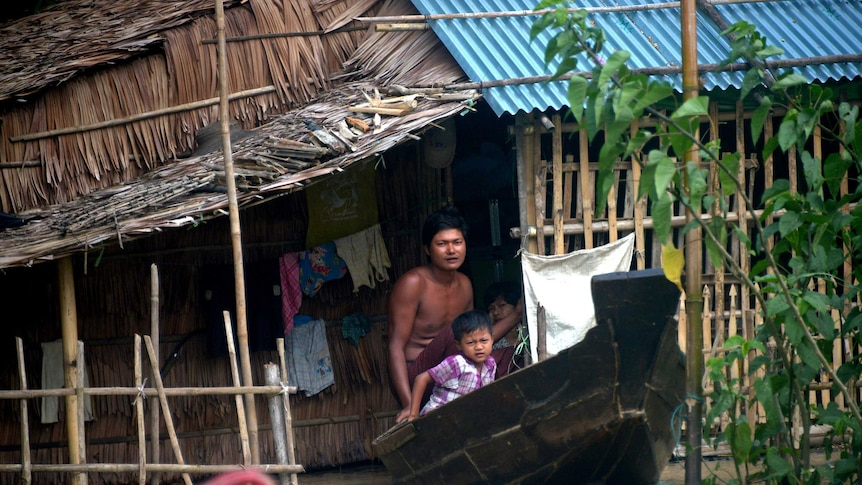 Resident commuting by boat through flooded water in Myanmar