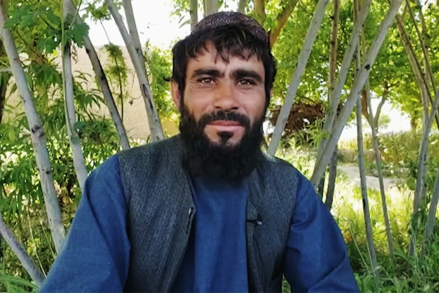 An Afghan man seated in front of green trees.