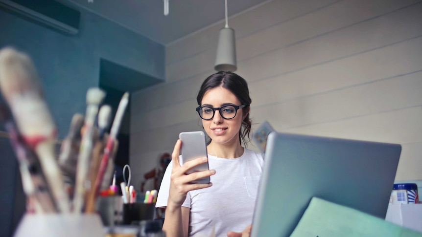 A young woman wearing glasses looks at her smartphone.  She sits in front of a laptop and paintbrushes