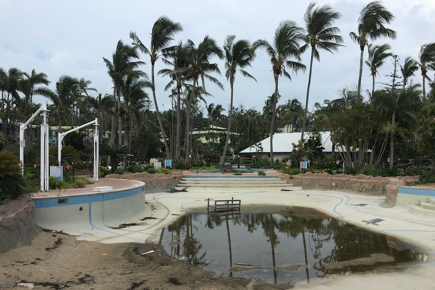 A near-empty pool complex with dirty water in the bottom