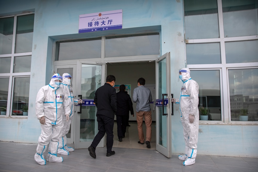 Security officers in protective suits hold the doors as government officials enter the visitors' hall