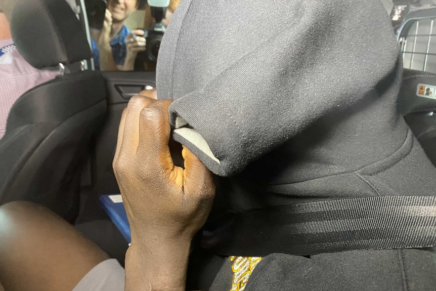 A handcuffed African man covers his face with a hoodie in back of a car with photographers behind.