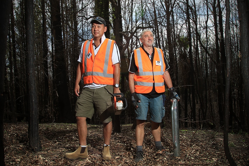 Doug Chang holds a chainsaw and Greg Murphy holds a post driver in burnt Kangaroo Valley bushland.