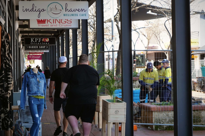 People walk down an outdoor shopping mall, which has been half fenced off for construction work