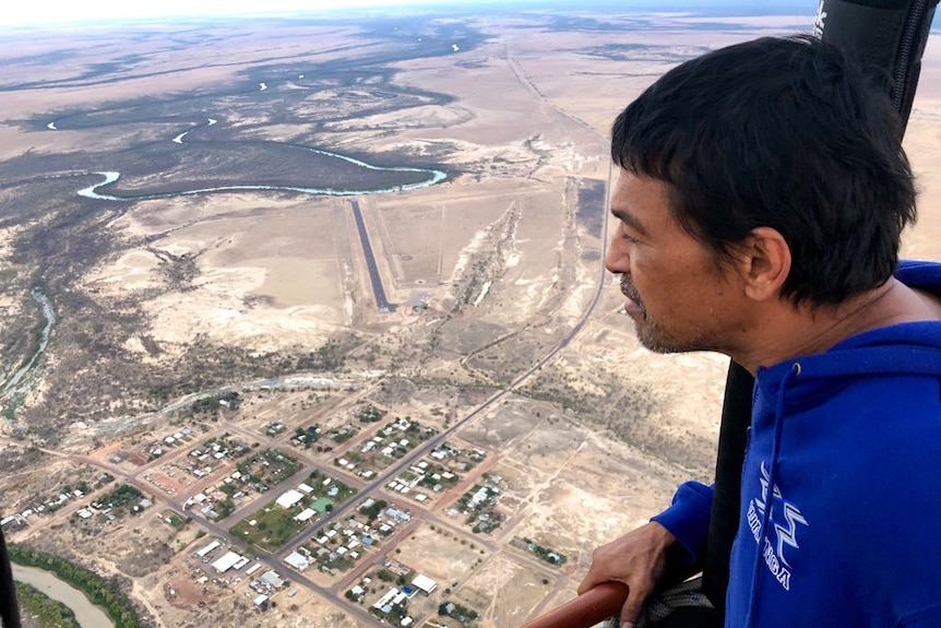 A native, dressed in a blue shirt, watches from a hot air balloon over a township and salt marshes