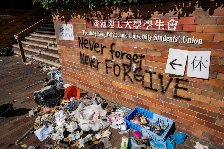 """Rubbish lies in front of a wall that reads """"never forgive, never forget""""."""