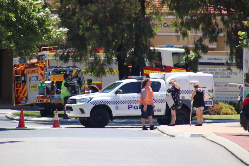 A police car blocks the road, with a fire truck pulled up nearby.