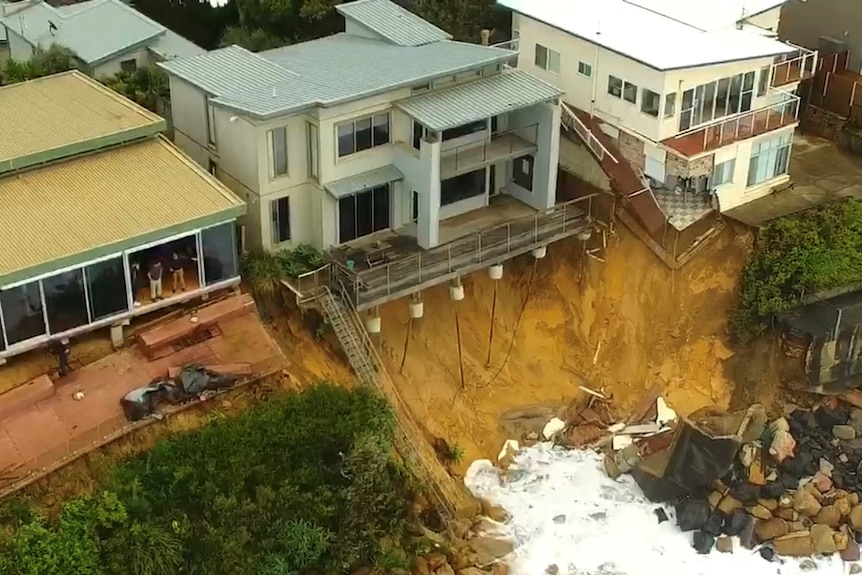 House foundations exposed and patios collapsed after surf ate away at the cliffs under homes