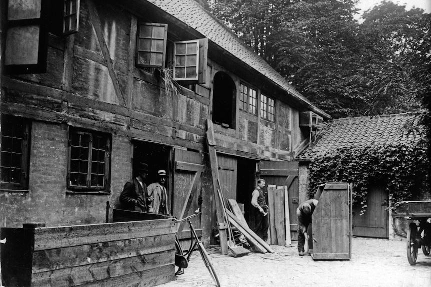 Wide black and white archive shot of men working on a house.