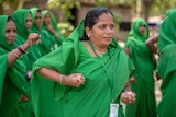 A woman in a green sari practices her karate moves