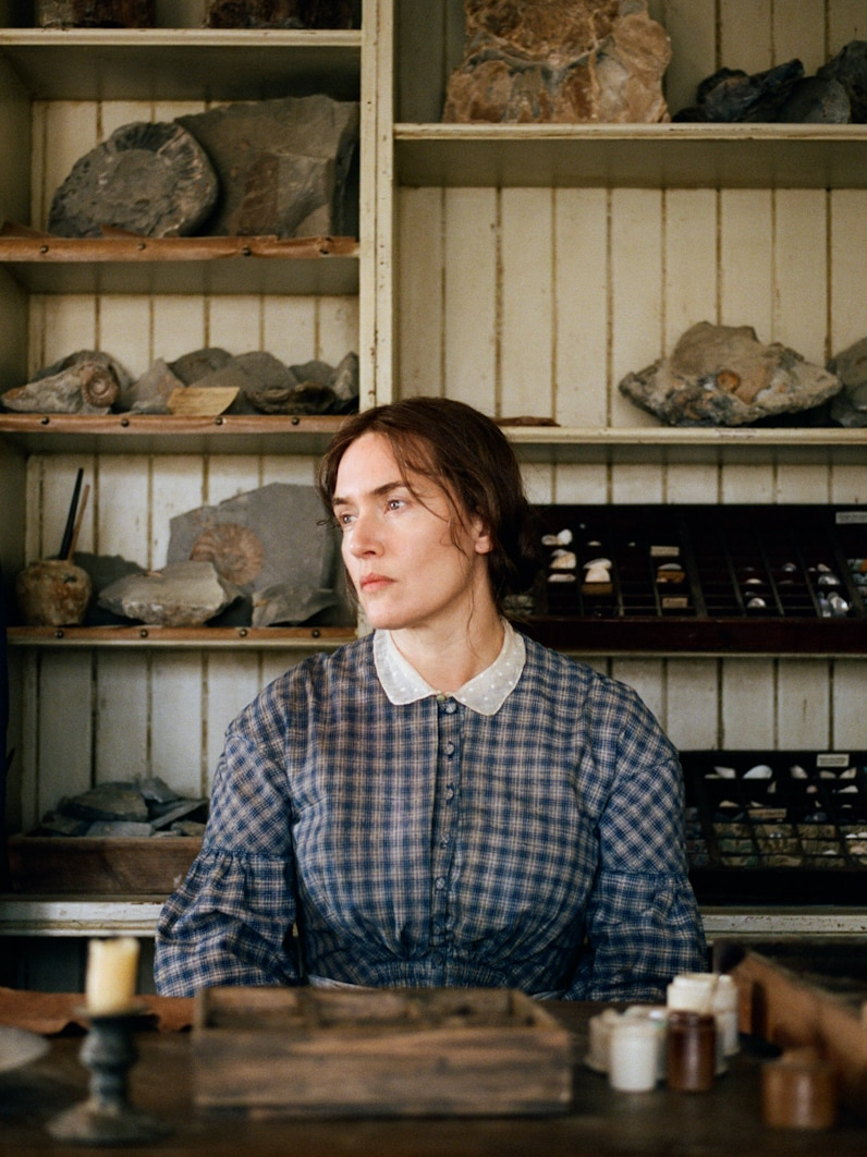 Kate Winslet wearing 19th century dress sits at desk with fossils on shelving behind her, turning left and staring into distance