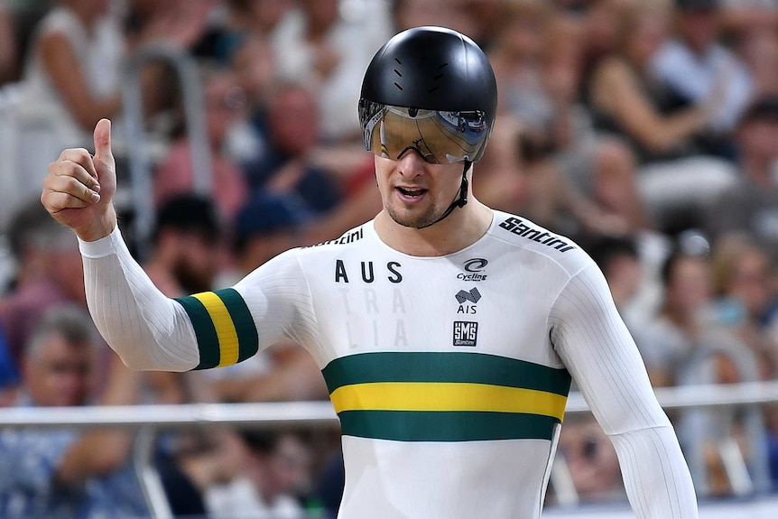 Matthew Glaetzer holds his thumb up, wearing a helmet and white track cycling suit with a gold and green band across the chest