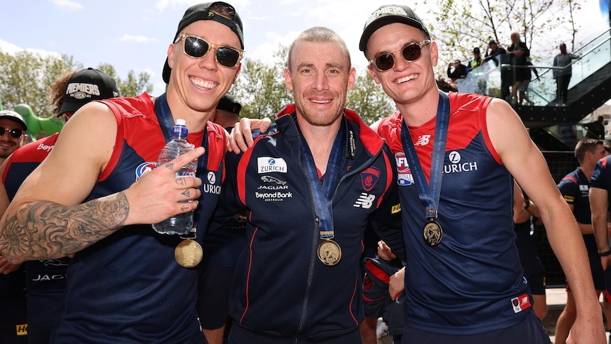 James Harmes, Simon Goodwin and Bayley Fritsch stand arm in arm. All have medals, and the two players are wearing sunglasses