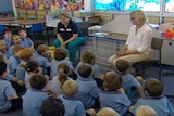 Generic TV still of anonymous Qld primary school children seated on floor of unidentified classroom