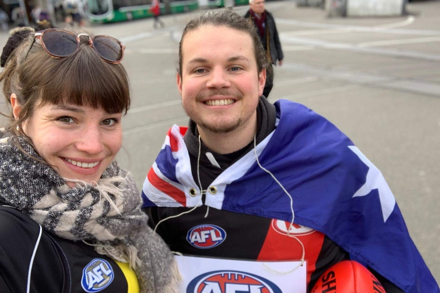 A woman stands next to a man wearing an Australian flag around his shoulders and holding and AFL ball.