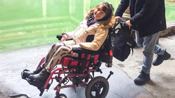 Young girl in wheelchair by Roman bath smiling at camera.