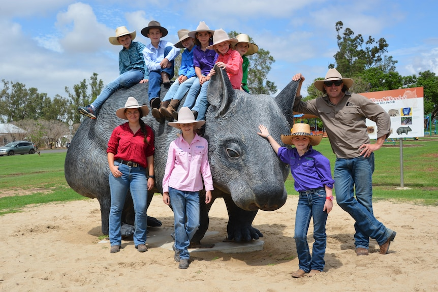 Giant wombat statue with people of varying ages sitting on and standing around it.