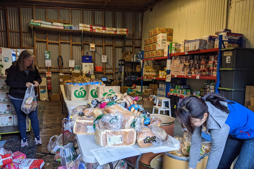 Two women add to a pile of food at a foodbank