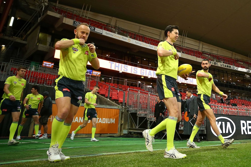 AFL umpires give signals as they step across the boundary line before a match.