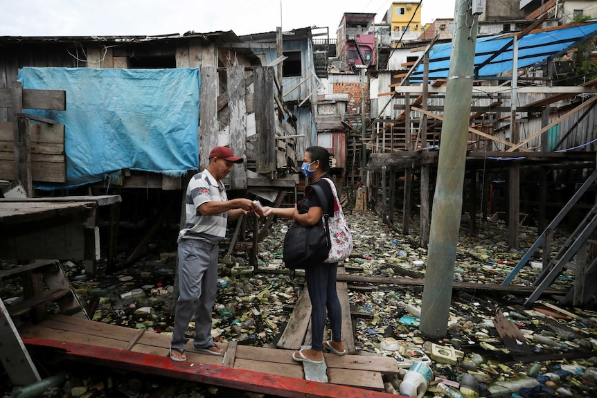 A man hands over a mask to a woman on a piece of wood against a background of run-down housing
