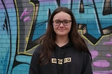 A teenage girl with long brown hair standing in front of a wall decorated in graffiti.