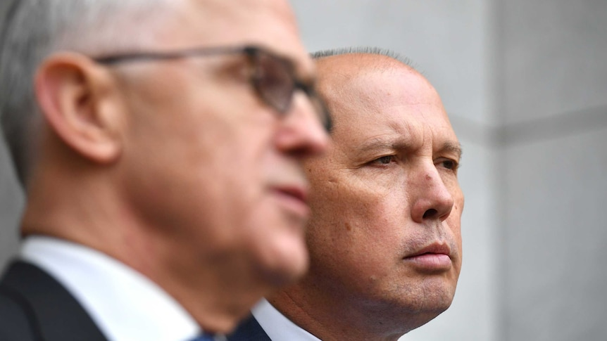Prime Minister Malcolm Turnbull (foreground) with Peter Dutton (background) at a press conference in Canberra.