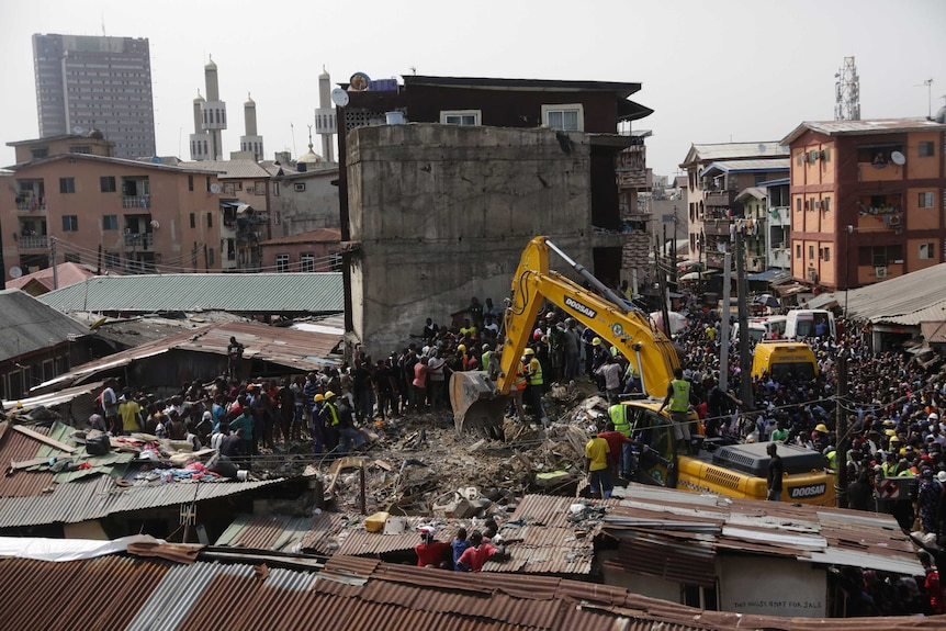 From an adjacent rooftop looking down, a vast crowd is packed into a tight Lagos city block with rubble in the centre of it.