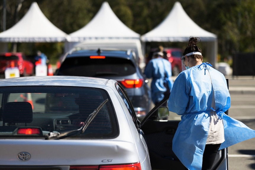 Health workers and cars at adrive-through COVID-19 testing clinic in Brisbane