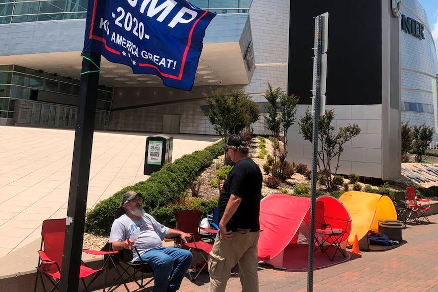Two men on camping chairs outside a convention centre with a Trump flag flying
