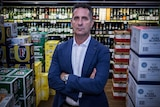A politician in a suit standing in a liquor store after making an announcement about a Banned Drinkers Register.