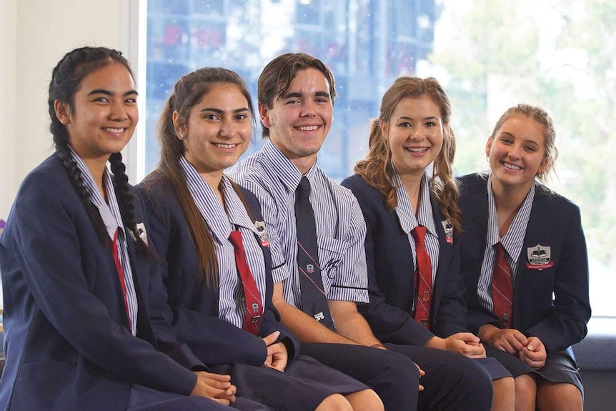 Five Year 12 students - four girls and a boy, from Mueller College, sit smiling as a group at Rothwell on Brisbane's northside.