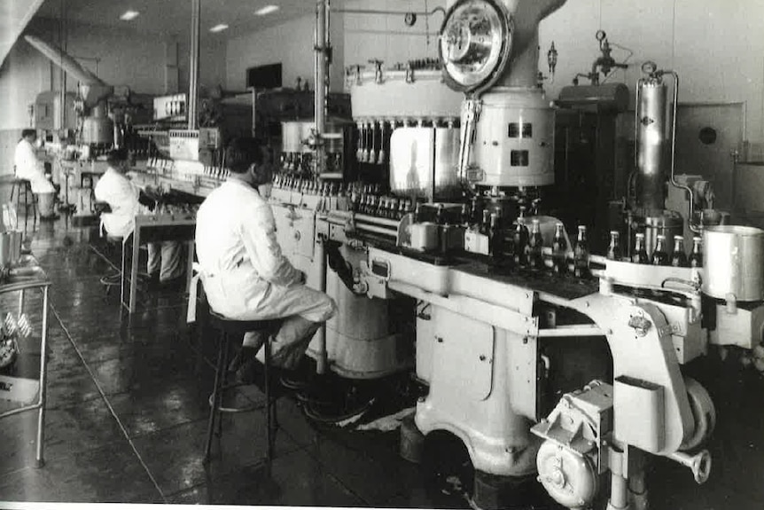 an old black and white photo of a factory with cola bottles