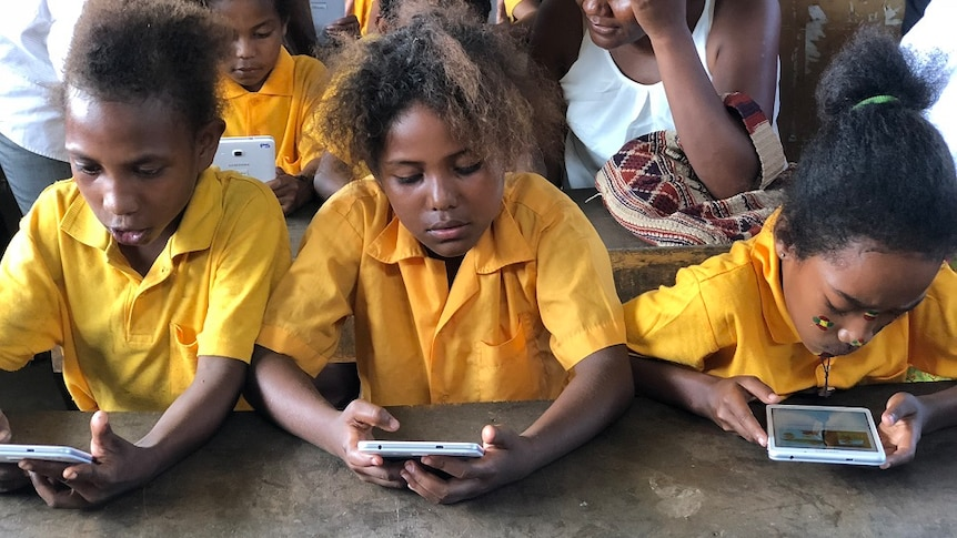School children in yellow uniforms read from the Library for All app.